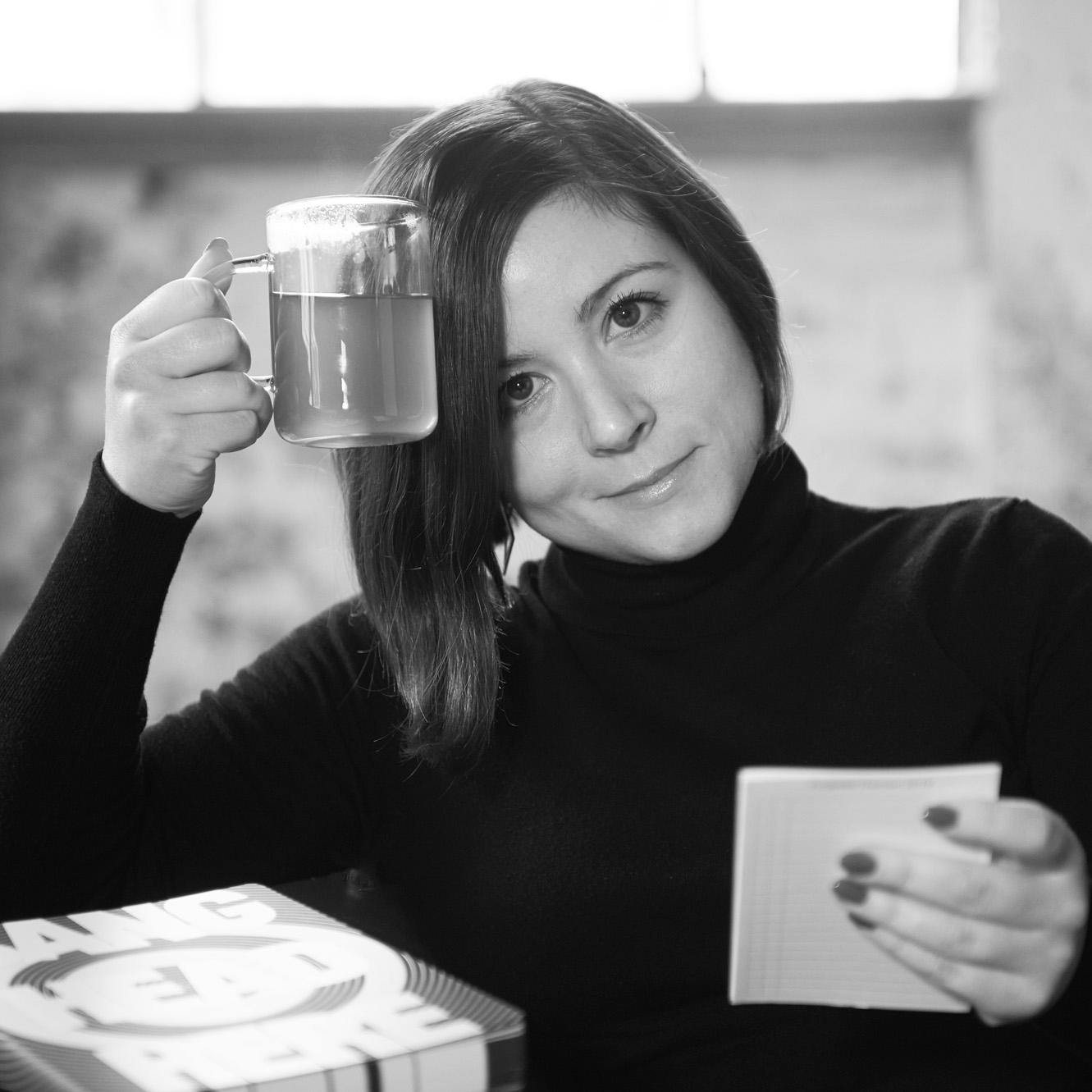 Portrait von Miss Metapher, sitzend auf einem Sofa mit Block und Teetasse