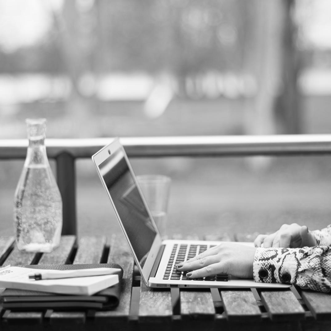 Außenaufnahme, Tisch, auf dem Laptop, Bücher und Wasserkaraffe stehen, Hände gleiten tippend über die Tastatur