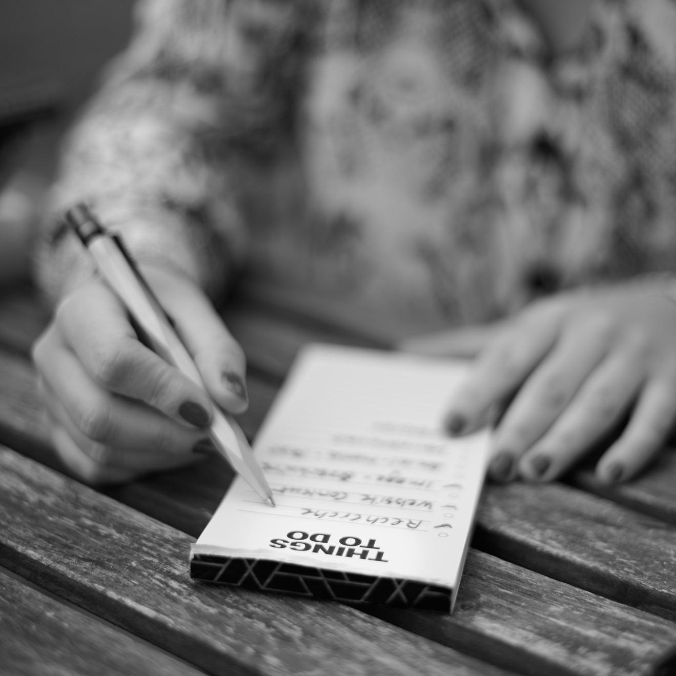 Block mit To-Do-Liste liegt auf dem Tisch und eine Hand schreibt darauf mit einem Pulli.